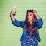 Señora de pelo largo hermosa con un smartphone cerca de un ladrillo verde Fotografía de archivo