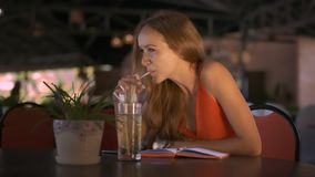 Señora de pelo largo rubia Sits en las sonrisas de la tabla del café