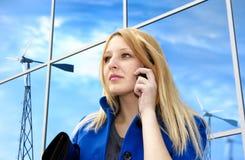 Señora del asunto con el teléfono cerca de windgenerators Foto de archivo libre de regalías