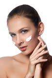 Señora del cuidado de piel que pone la crema de cara Muchacha morena atractiva en w Imágenes de archivo libres de regalías