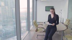 Señora del negocio de la muchacha en la oficina en un rascacielos almacen de metraje de vídeo