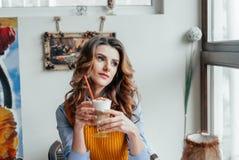 Señora del negocio en latte de consumición del café imagenes de archivo