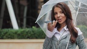 Señora del negocio en sombrero negro con el paraguas en su mano que envía el mensaje audio de la voz en el teléfono móvil en habl almacen de video