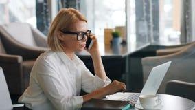 Señora del negocio maduro que hace llamada telefónica móvil y que usa el ordenador portátil en café almacen de metraje de vídeo
