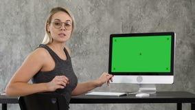 Señora del negocio que habla con la cámara en la oficina que señala a la pantalla en el ordenador Exhibición verde de la maqueta  metrajes