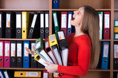 Señora del negocio que sostiene la pila grande de carpetas de la oficina Imagen de archivo