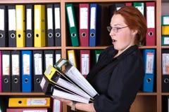 Señora del negocio que sostiene la pila grande de carpetas de la oficina Foto de archivo