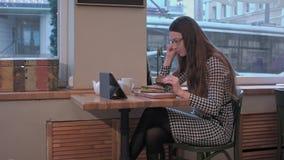 Señora del negocio que usa la tableta mientras que come el bocadillo en el café almacen de metraje de vídeo