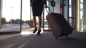 Señora del negocio que va de aeropuerto con su equipaje Mujer en talones que camina con su maleta del terminal a la calle de la c almacen de metraje de vídeo