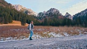 Señora delgada joven Walking en el camino hermoso en montañas Cámara lenta cinemática almacen de metraje de vídeo