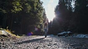 Señora delgada joven Walking en Forest Road Cámara lenta con la llamarada de Sun Lense almacen de metraje de vídeo