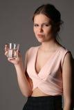 Señora descontenta con el vidrio de agua Cierre para arriba Fondo gris Fotos de archivo libres de regalías