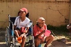 Señora discapacitada en la silla de ruedas con otros mendigos masculinos en la yarda de la iglesia que piden limosnas foto de archivo