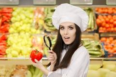 Señora divertida Chef Inspecting Vegetables con la lupa Foto de archivo libre de regalías
