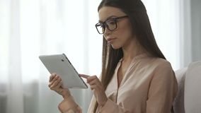 Señora elegante en vidrios que analiza las letras del correo electrónico, comprobando la carpeta del buzón de entrada en la table metrajes