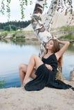 Señora elegante hermosa en el vestido abierto que descansa cerca del lago Imágenes de archivo libres de regalías
