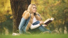 Señora elegante que lee el libro de la aventura en Central Park, sentándose debajo de árbol, otoño almacen de video