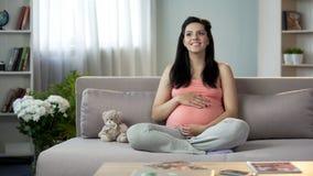 Señora embarazada inspirada que frota ligeramente la panza, soñando con lo más pronto posible el aspecto de recién nacido fotografía de archivo libre de regalías