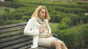 Señora embarazada preocupante que respira profundamente, banco que se sienta, dolor de la panza, contracciones almacen de metraje de vídeo