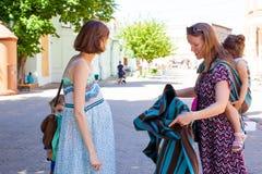 Señora embarazada que aprende cómo utilizar el abrigo del bebé imagen de archivo