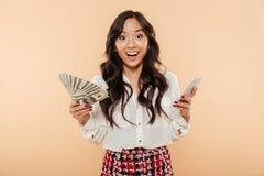 Señora emocionada que sostiene la fan de 100 billetes de dólar en un mano y tre Imagenes de archivo