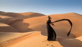 Señora en abaya en dunas de arena Imágenes de archivo libres de regalías