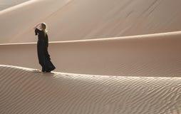 Señora en abaya en dunas de arena Fotos de archivo libres de regalías