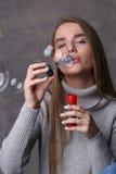 Señora en burbujas que soplan del jersey Cierre para arriba Fondo gris Foto de archivo libre de regalías