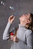 Señora en burbujas que soplan del suéter Cierre para arriba Fondo gris Imagen de archivo
