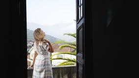 Señora en el balcón del chalet entre las colinas en pueblo almacen de video