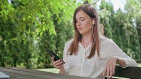 Señora en el parque que escucha la música en el teléfono almacen de metraje de vídeo