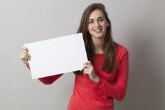 Señora en el rojo que sostiene el tablero o el papel en blanco para su anuncio Imagen de archivo libre de regalías