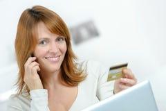 Señora en el teléfono móvil que sostiene la tarjeta de crédito imagen de archivo libre de regalías