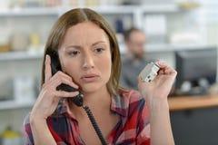 Señora en el teléfono que parece preocupado Foto de archivo libre de regalías