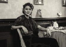 Señora en el vestido de noche que se sienta en la tabla Foto de archivo libre de regalías