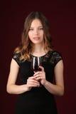Señora en el vestido que sostiene el vidrio de vino Cierre para arriba Fondo rojo oscuro Fotografía de archivo