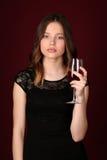 Señora en el vestido que sostiene la copa Cierre para arriba Fondo rojo oscuro Imágenes de archivo libres de regalías
