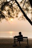 Señora en la puesta del sol en la playa Fotografía de archivo