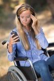 Señora en la silla de ruedas que desconcierta sobre el teléfono móvil Foto de archivo libre de regalías