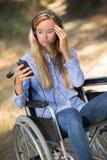 Señora en la silla de ruedas que mira en la confusión el teléfono móvil Imagenes de archivo