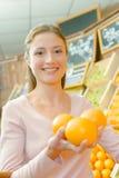 Señora en la tienda que sostiene tres naranjas disponibles Foto de archivo