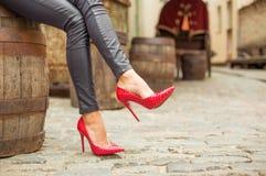 Señora en pantalones de cuero negros y zapatos rojos del tacón alto imagenes de archivo