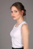 Señora en perfil derecho de la camiseta blanca Cierre para arriba Fondo gris Imagen de archivo