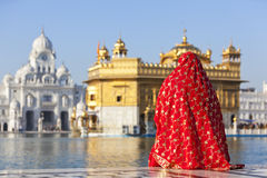 Señora en sari roja en el templo de oro. Foto de archivo