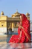 Señora en sari roja en el templo de oro. Imagen de archivo libre de regalías