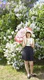 Señora en sombrero con el paraguas cerca de la lila Foto de archivo