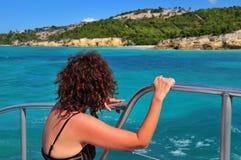 Señora en un barco que mira una isla fotografía de archivo