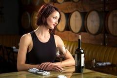 Señora en un restaurante de lujo costoso con una botella de con clase elegante del vino Foto de archivo libre de regalías