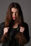 Señora en una chaqueta de cuero tachonada que se sostiene el pelo Cierre para arriba Fondo blanco Fotografía de archivo libre de regalías