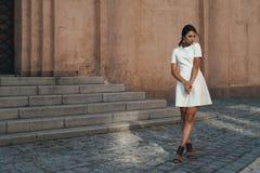 Señora en vestido contra el edificio antiguo con mirada pensativa Fotografía de archivo libre de regalías